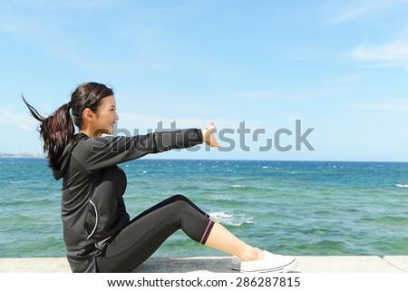 Women who exercises beside the sea