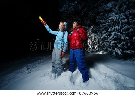 Women with backpacks exploring deep wild forest at night with a torch