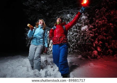 Women with backpacks exploring deep wild forest at night with a torch and red flare
