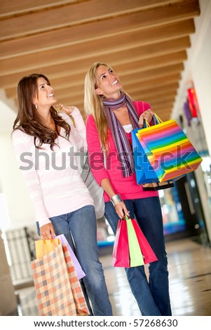 Women with bags walking at a shopping center  and smiling
