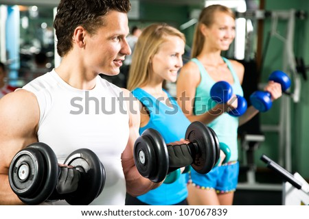 Women with  fitness trainer in the gym exercising with dumbbells
