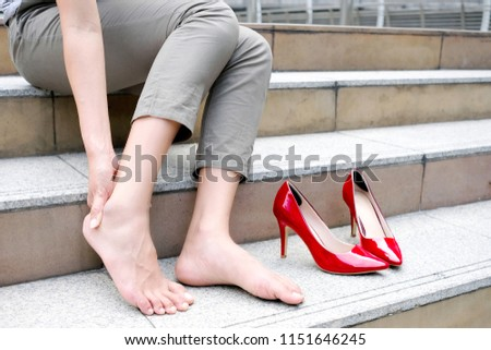 Women with leg cramps and ankles from high heels. She sat on the stairs holding her leg. and catch her foot and she has foot pain. Caused by wearing high heels. Health and beauty concept #1151646245