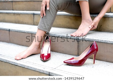 Women with leg cramps and ankles from high heels. She sat on the stairs holding her leg. and catch her foot and she has foot pain. Caused by wearing high heels. Health and beauty concept #1439529647