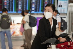 women with luggage and trolley is wearing medical face masks to protect themselves from pollution, germs and covid19 coronavirus at the airport.