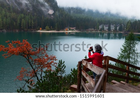 Women with red rain jacket enjoying the peaceful mystic view of a mountain lake with cloudy dramatic mountains in the background on a rainy autumn day. Taking pictures with her mobile phone.