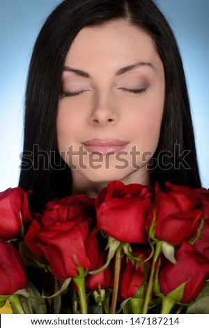 Women with red roses. Beautiful middle-aged women holding a bunch of red roses and keeping her yes closed while isolated on blue