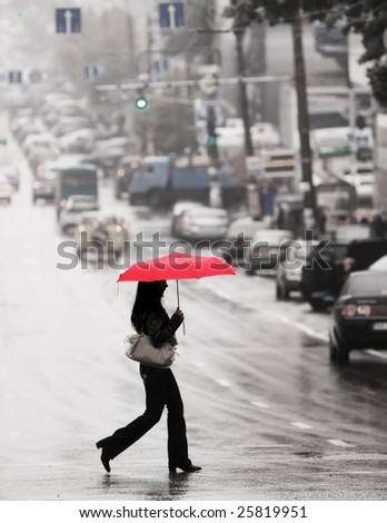 women with red umbrella cross the street in the rain
