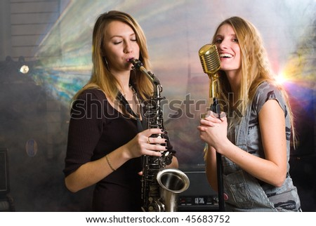 women with saxophone and microphone at concert - stock photo