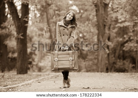 Women with suitcase at outdoor. Photo in sepia style.