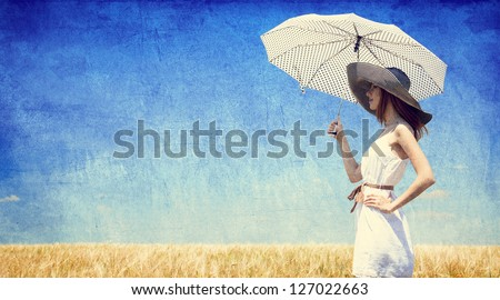 women with umbrella at wheat...