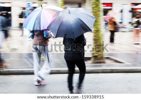 women with umbrellas walking with umbrellas in the rainy city