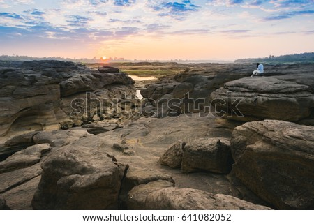 Women with white shirt sitting on a rock in Thailand stone canyon or Sam Pan Boak. Ubonratchathani Province ,Thailand #641082052