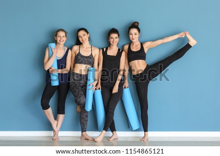 Women with yoga mats near color wall #1154865121