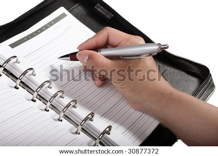 Women witting an appointment in a personal planner - stock photo