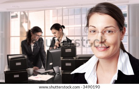 Women work in brightly lit office. Daylight, indoor, office.