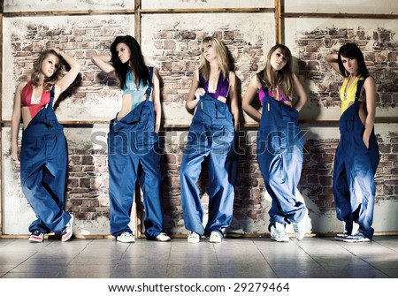 Women worker team. Five young women on wall background.