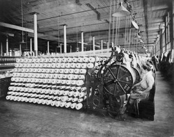 Women working at textile machines, beaming and inspecting yarn, at the American Woolen Company, Boston. The beaming process prepares the warp, the lengthwise fibers of a woven fabric. Ca. 1910.