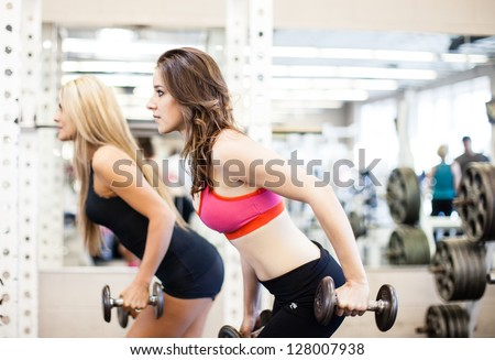 Women working on their triceps with dumbbells at the gym