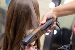 Womens hairdresser, beauty salon. hairdresser makes curls with a curling iron
