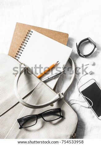Womens leather handbag, clean blank notepad, pen, glasses, smartphone,  watch on a light background, top view. Free space for text. Female workplace business background