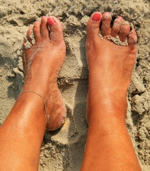 Womens sandy feet on beach