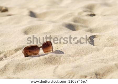 Womens sunglasses on bright sunny beach.