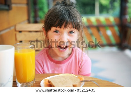 Wondered child girl has a healthy breakfast outdoors