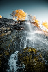 Wonderful and beautiful waterfall in the german mountains with golden autumn tones on a bright sunny day. Wild mountain river with water splash. Harz Mountains, Harz National Park in Germany.