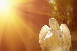 wonderful angel in the rays of the sun (architecture, statue, archetype, religion, faith concept)