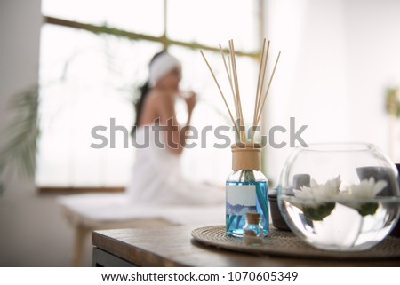 Wonderful aroma. Selective focus of aroma sticks with a beautiful relaxed woman enjoying their smell in the background