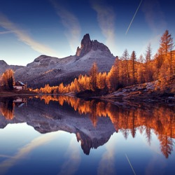 Wonderful autumn landscape during sunset. Fairy tale moutain lake with picturesque sky, majestic rocky mount and colorful trees glowing sunlight. Amazing nature scenery. Federa lake. Dolomites Alps.