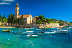 Wonderful bay with beach and boats. Spectacular walkway and stone church with tower on the waterfront, Hvar, Hvar island, Dalmatia, Croatia, Europe