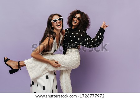 Wonderful black girl in black blouse and trendy white pants laughing and having fun with her friend in sunglasses on isolated backdrop.