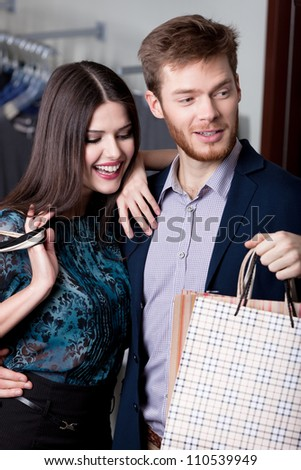 Wonderful couple is in the shopping mall and happy that they bought a lot of things at cut rates