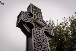 Wonderful embossed Celtic stone cross, full of details and textures in its elaborate carvings and lichen growing.