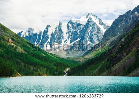 Wonderful giant snowy mountains. Creek flows from glacier into mountain lake. Shine water in highlands. White clear snow on ridge. Amazing atmospheric landscape of majestic nature.