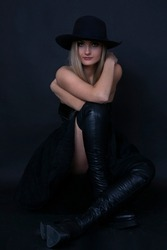 Wonderful girl in dark dress and hat posing on black background.