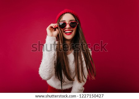 Wonderful girl in trendy heart glasses expressing good emotions. Glamorous caucasian woman in hat isolated on claret background and laughing. #1227150427