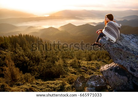 Wonderful landscape with cloud inversion. Relaxing, feeling alive, breathing fresh air, got freedom from work, calm and dreaming Sea of clouds. Hiker relaxing on top of a mountain and enjoying sunrise #665971033