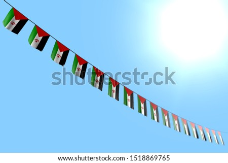 wonderful many Western Sahara flags or banners hanging diagonal on rope on blue sky background with soft focus - any holiday flag 3d illustration