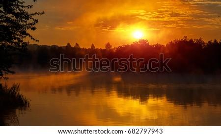 Shutterstock wonderful misty evening. majestic golden sunset over the foggy lake. picturesque dramatic scene. unusual amazing scenery. creative image