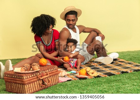 Wonderful moments together. Happy african american family having picnic against yellow studio background. Leisure, togetherness, relationship, childhood and human emotions concept.