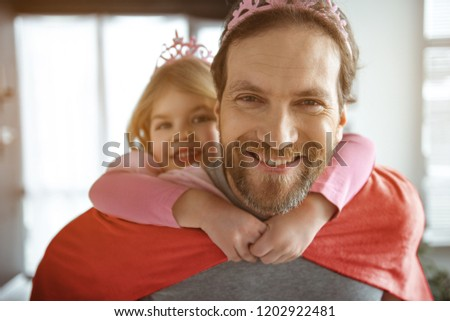 Wonderful moments together. Portrait of happy father carrying girl on shoulders. He is looking at camera and smiling. Man is wearing crown and mantle