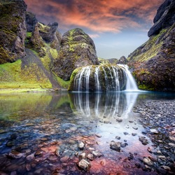 Wonderful nature of Iceland. fantastic view on canyon with green grass and icelandic moss near river with waterfall. Tipical Icelandic scenery. Stjornarfoss Waterfall during sunset with reflections.