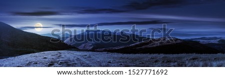 wonderful panorama of mountain ridge in autumn. gorgeous landscape with rolling  hills and meadows in weathered grass in full moon light. sunny weather with fluffy clouds on the sky at night