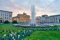 Wonderful panoramic view over colorful tulips in green grass past a fountain on the Berlin Brandenburg Gate in the sunset with beautiful clouds. Spring time in Germany - paris square in Berlin city