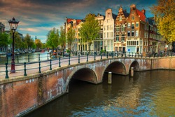 Wonderful spring cityscape, Amsterdam water canals and typical dutch houses on spectacular sunset, Netherlands, Europe