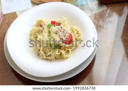 Wonderful still life with delicious cheese herbs and pasta with meat and tomatoes. Business lunch in a cafe.