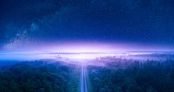Wonderful summer night landscape, starry sky and pine forest, through which the railway line runs. Mystical or magical atmosphere.