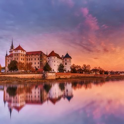 Wonderful sunrise view of Schloss Hartenfels, with colorful sky reflected in Elbe river . Picturesque morning view of castle on banks of the Elbe.  Torgau. Saxony, Germany. creative Scenic image.